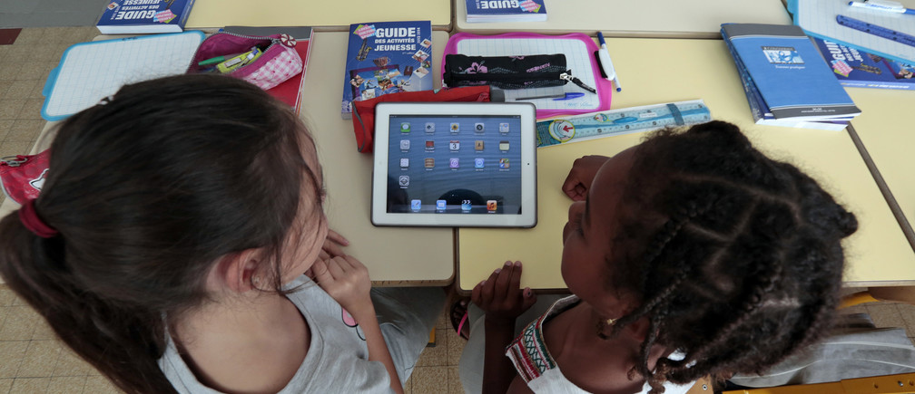 Elementary school children share an electronic tablet on the first day of class in the new school year in Nice, September 3, 2013