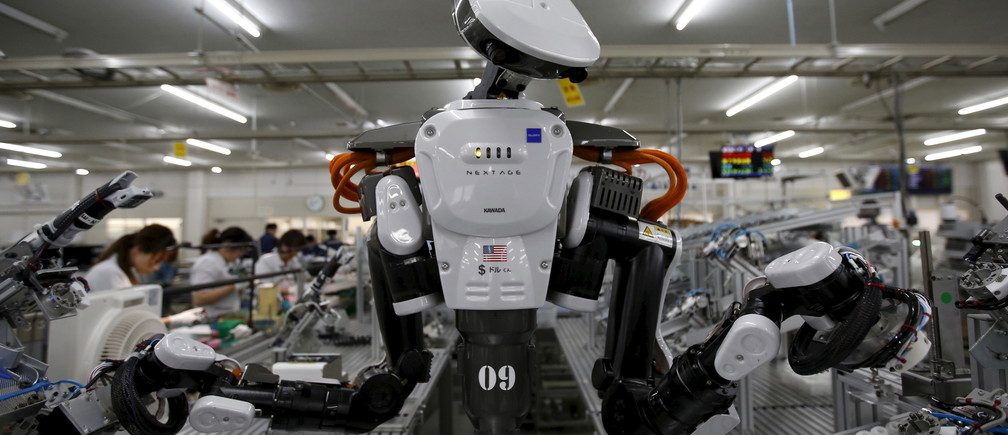 A humanoid robot works side by side with employees in the assembly line at a factory of Glory Ltd., a manufacturer of automatic change dispensers, in Kazo, north of Tokyo, Japan, July 1, 2015. Japanese firms are ramping up spending on robotics and automation, responding at last to premier Shinzo Abe's efforts to stimulate the economy and end two decades of stagnation and deflation. Picture taken July 1, 2015. REUTERS/Issei Kato      TPX IMAGES OF THE DAY      - RTX1IU6U