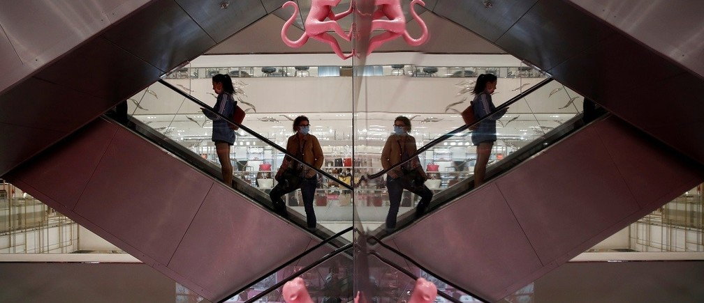 Customers, wearing protective face masks, are reflected in a mirror as they stand on an escalator inside the department store Le Printemps Haussmann in Paris as France eases gradually its lockdown measures and restrictions following the outbreak of the coronavirus disease (COVID-19) in France, May 28, 2020. REUTERS/Gonzalo Fuentes     TPX IMAGES OF THE DAY - RC2MXG9TH697