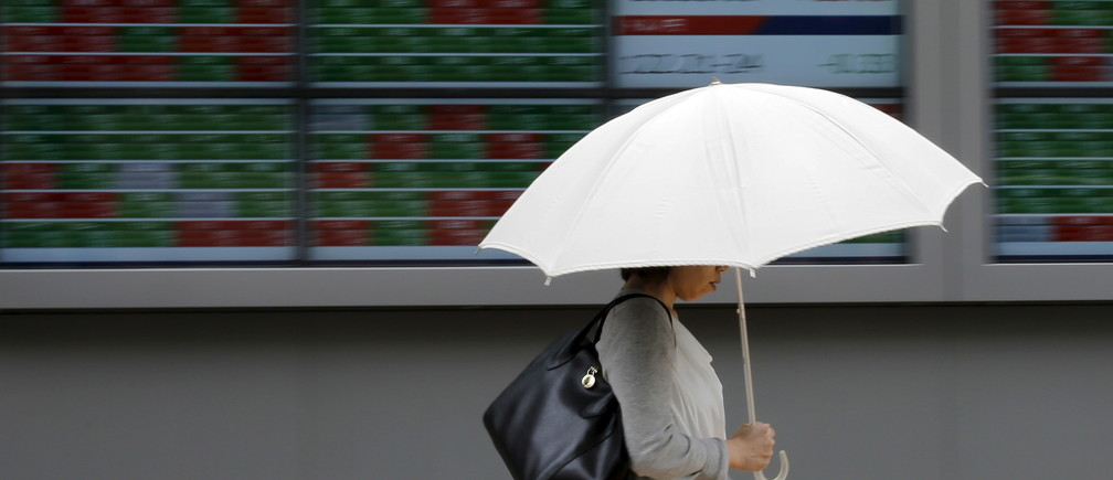 A woman holding a parasol walks past a stock quotation board outside a brokerage in Tokyo, June 30, 2015.