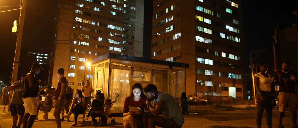 Carolina Gutierrez (center L), 17, and Neuil Valdez, 18, use mobile phones to connect to the internet at a hotspot in downtown Havana, Cuba, December 12, 2016. REUTERS/Alexandre Meneghini - RTX2UQOG