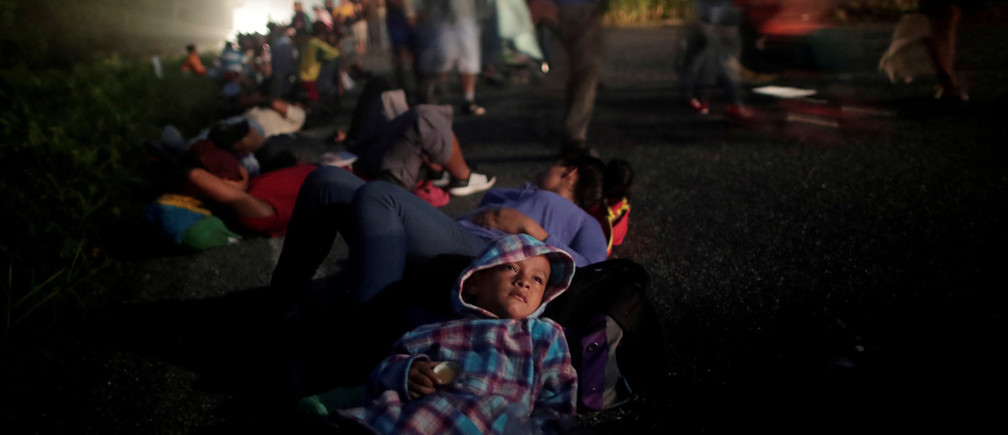 "Glenda Escobar, 33, a migrant from Honduras, part of a caravan of thousands from Central America en route to the United States, rests on the road with her son Adonai, as they make their way to Pijijiapan from Mapastepec, Mexico, October 25, 2018. Reuters photographer Ueslei Marcelino: ""We accompanied Glenda and her two children for 24 hours. Adonai told me that he would stay awake every night so his mother could rest. In this photo, I got one of the rare moments that remained quiet for some time. He would not stop for a minute - always smiling, jumping or running. I believe that his good-nature and positive energy, became the 'fuel' for his brother and his mother to continue the walk."" REUTERS/Ueslei Marcelino  SEARCH ""IMMIGRATION POY"" FOR THIS STORY. SEARCH ""REUTERS POY"" FOR ALL BEST OF 2018 PACKAGES. TPX IMAGES OF THE DAY. - RC14AD4097D0"