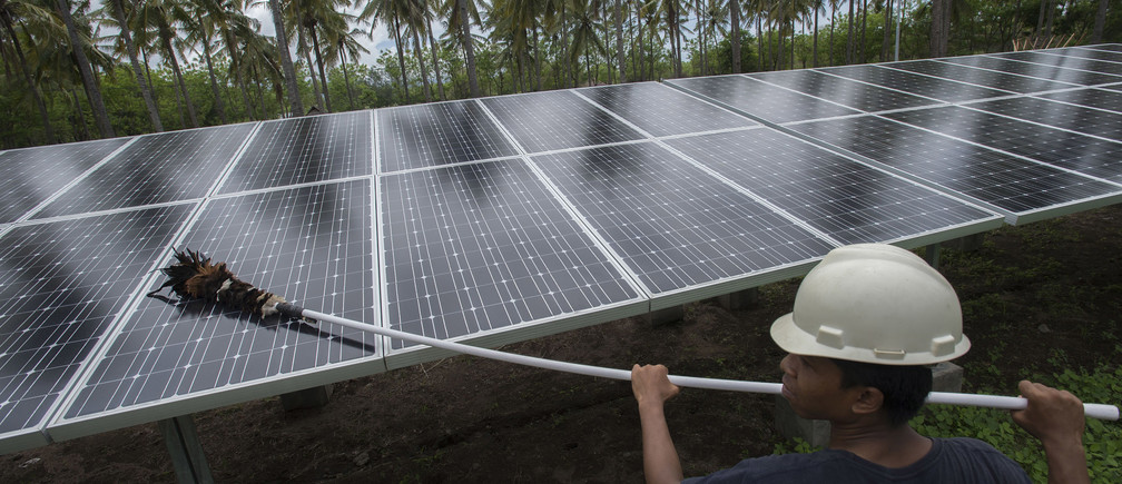 An employee cleans panels at a solar power plant on Gili Meno island, Indonesia.