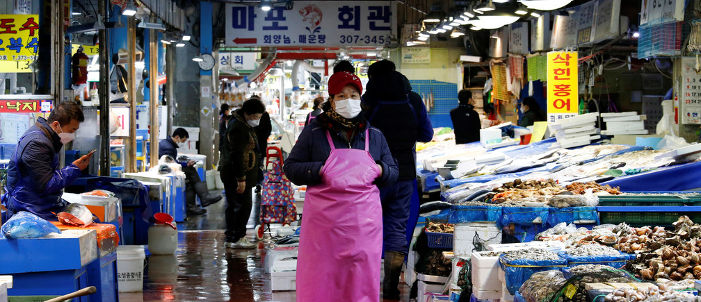 A shopkeeper wearing a mask to prevent contracting the coronavirus waits for a customer at a traditional market in Seoul, South Korea, February 27, 2020.    REUTERS/Heo Ran - RC2R8F9M8Y4S