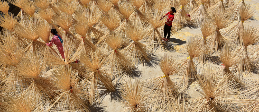 Employees from a bamboo industry company dry semi-finished bamboo chopsticks in a village in Xingan county, Jiangxi province, China July 16, 2017. Picture taken July 16, 2017. REUTERS/Stringer      ATTENTION EDITORS - THIS IMAGE WAS PROVIDED BY A THIRD PARTY. CHINA OUT. NO COMMERCIAL OR EDITORIAL SALES IN CHINA. - RC1F636F6930