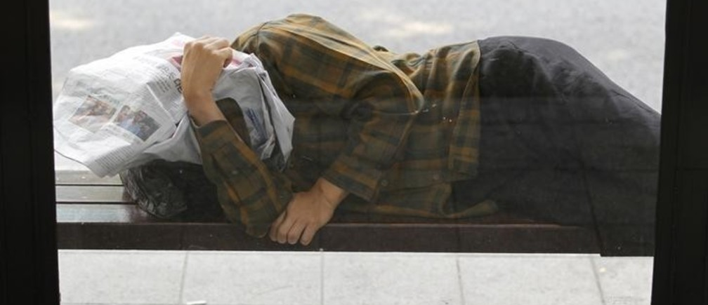 A homeless man takes a nap at a bus stop in central Seoul June 19, 2012. Asian shares edged down on Tuesday as rising Spanish bond yields stoked fears its tottering banking system is dragging Madrid deeper into crisis, snuffing out a relief rally that followed a win for mainstream parties in Greece's weekend election.  REUTERS/Lee Jae-Won (SOUTH KOREA - Tags: BUSINESS EMPLOYMENT)