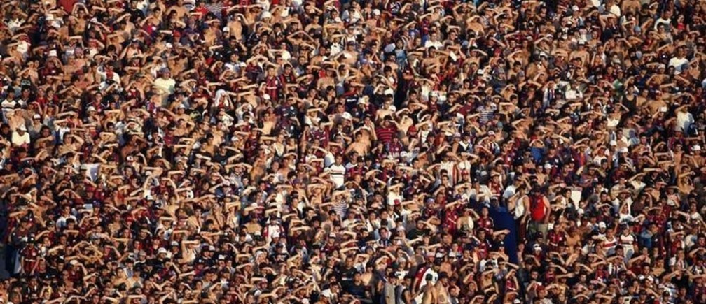 San Lorenzo's fans use their hands to block the sun during their Argentine First Division soccer match against Estudiantes in Buenos Aires December 1, 2013. REUTERS/Marcos Brindicci (ARGENTINA - Tags: SPORT SOCCER)