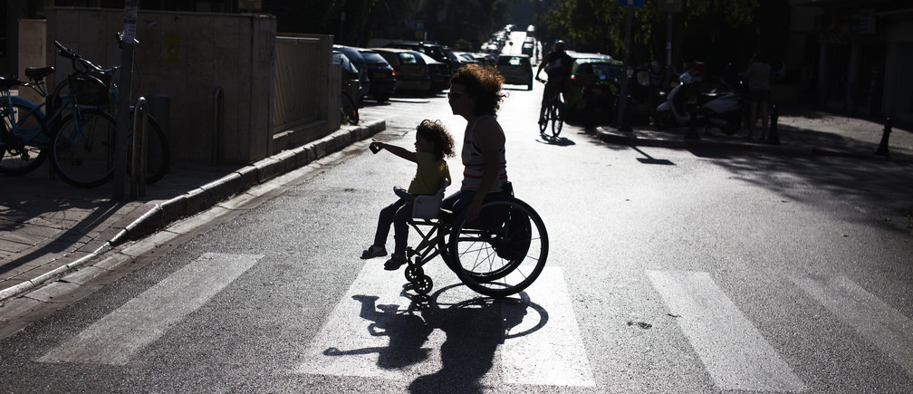 Pascale Bercovitch carries her daughter Mica, 3, on her wheelchair as they cross a road near their home in Tel Aviv May 16, 2012. Bercovitch, 44, who lost her legs in a train accident in France in 1984, will represent Israel at the London Paralympics in hand cycling events.  Picture taken May 16, 2012. REUTERS/Nir Elias (ISRAEL - Tags: SPORT OLYMPICS SOCIETY) - RTR34SPK
