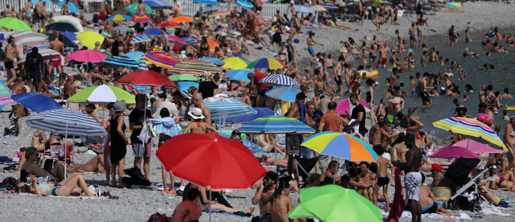 Parasols dot a crowded beach with sunbathers in Nice as summer temperatures continue and authorities maintain a heat wave alert in France, August 1, 2018.