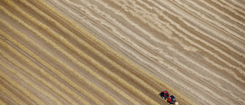 An aerial view shows a French farmer in his tractor making bales of straw after wheat harvest in his field in Coquelles near Calais, northern France, July 21, 2015. Wheat crops in Western Europe have coped relatively well with dry and sweltering conditions in the past month, keeping the region on course for a large harvest, analysts said. In the European Union's top wheat producer France, where harvesting is in full flow, results so far indicated decent yields, albeit shy of very high potential during spring.   REUTERS/Pascal Rossignol  TPX IMAGES OF THE DAY - PM1EB7L1C8801