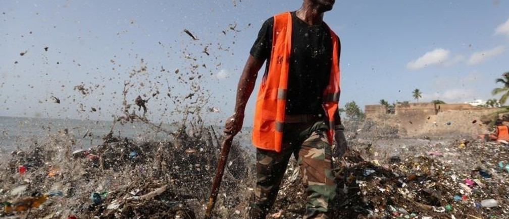 A soldier walks on the shores of Montesinos beach, which is covered in plastic and other debris, during a cleanup in Santo Domingo, Dominican Republic July 19, 2018. REUTERS/Ricardo Rojas - RC122A599800