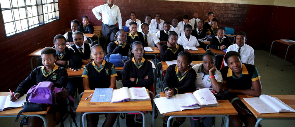 Teacher Reginald Sikhwari poses for a picture with his class of grade 11 students at Sekano-Ntoane school in Soweto, South Africa, September 17, 2015.