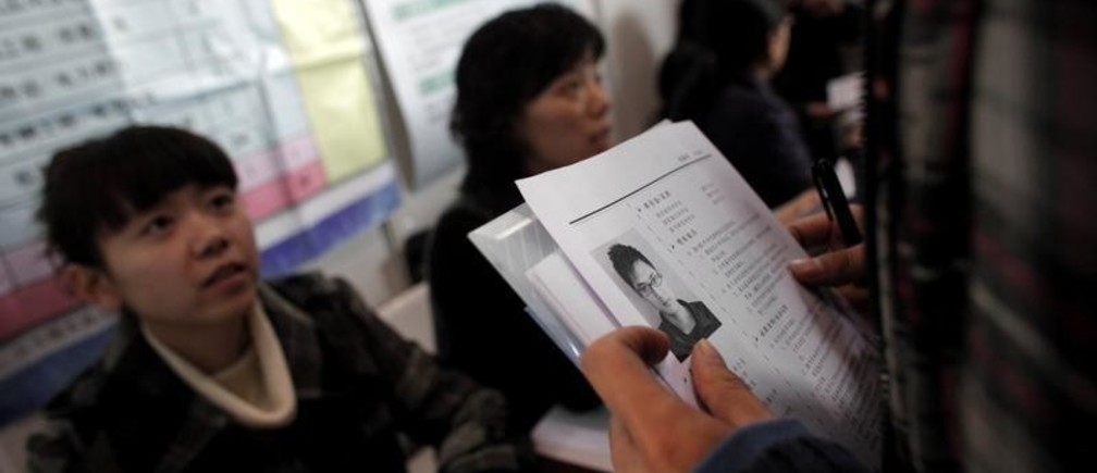 A student holds his resume as he looks for a job during a job fair at a university in Shanghai December 10, 2010.