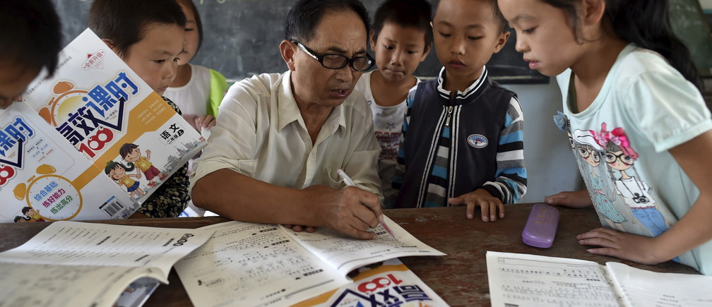 """A teacher (C) speaks to students inside a classroom of Dalu primary school in Gucheng township of Hefei, Anhui province, China, September 8, 2015. The school, opened in 2006 and has never acquired a legal license, may face a shutdown order from the government. There are currently over 160 students in the school, mostly """"leftover children"""", whose parents left their hometown to earn a living, local media reported. Picture taken September 8, 2015. REUTERS/Stringer CHINA OUT. NO COMMERCIAL OR EDITORIAL SALES IN CHINA  - GF10000198778"""