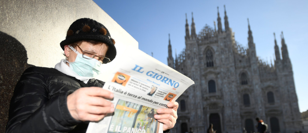 A woman reads a newspaper outside Duomo cathedral, closed by authorities due to a coronavirus outbreak, in Milan, Italy February 24, 2020. REUTERS/Flavio Lo Scalzo - RC2W6F9F4X01