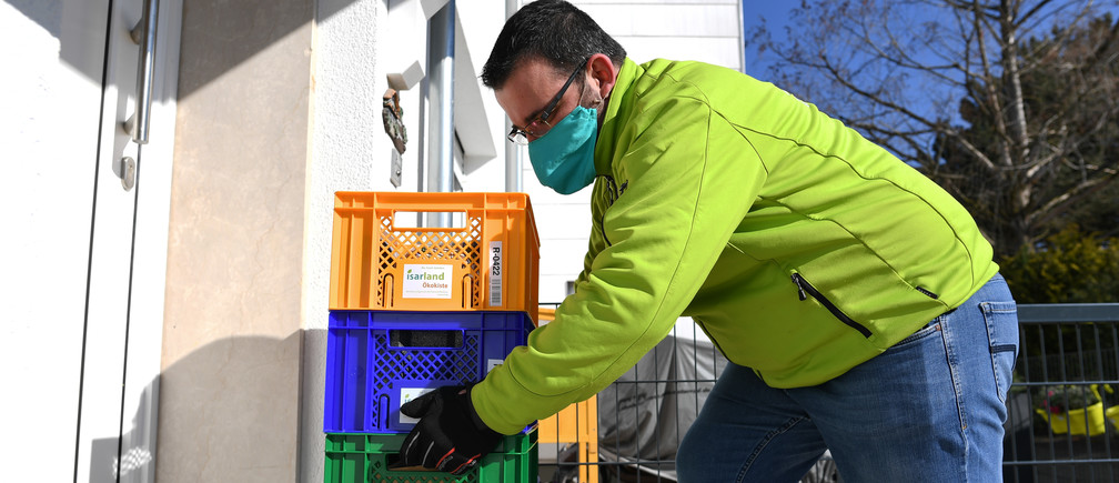 "Konstantinos Papadopoulos of the ""Isarland Oekokiste"", an organic delivery service for Munich and the south-eastern region, delivers products to a customer, as the spread of the coronavirus disease (COVID-19) continues, in Unterhaching, Germany, April 1, 2020. REUTERS/Andreas Gebert - UP1EG410PFHK9"