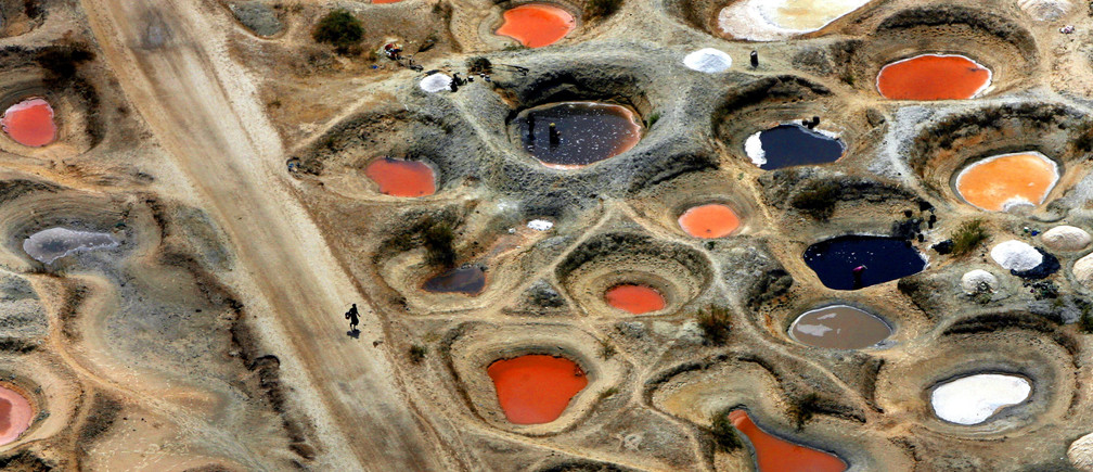 An aerial view shows pools of mineral-coloured water gathered on salt flats in holes dug by salt collectors on the Senegalese coastline near the border with Gambia June 12, 2006. Women collect salt by hand into 50kg (110lbs) sacks, which sell for about $2, and are traded with neighbouring Gambia and Mauritania, where salt is mainly used for preserving fish in areas without electricity. REUTERS/Finbarr O'Reilly (SENEGAL)FOR BEST QUALITY also see: GF1DSWQOEXAA - RTR1EDG8