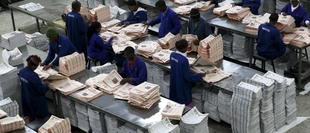Workers arrange copies of the Business Daily newspaper produced by the Nation Media Group at a printing press plant on the outskirts of Kenya's capital Nairobi, November 24, 2015.