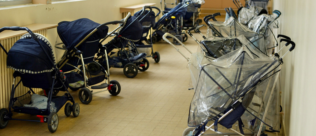 Pushchairs are parked at the entrance of a day-nursery in Vincennes, near Paris, April 30, 2003. French government announced April 29, a boost in state aid to young families with a payment of 800 euros ($878) to all mothers-to-be and a drive to create 20,000 more places in public creches. - RTXLXPO