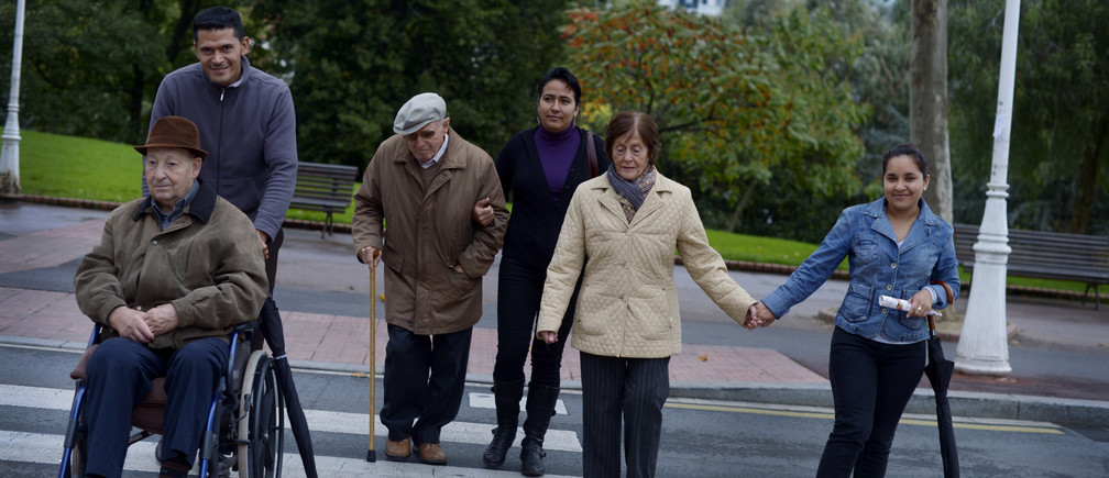 Elderly people are helped across the road by their Nicaraguan assistants during an excursion to Dona Casilda park in Bilbao October 26, 2012.    REUTERS/Vincent West (SPAIN - Tags: SOCIETY) - GM1E8AR02NL01