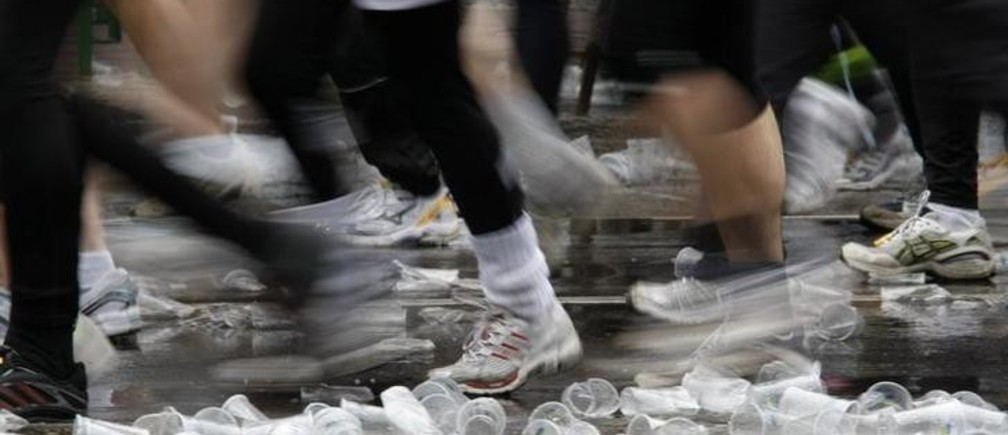 Runners run over plastic cups near a refreshment stop during 28th Berlin half-marathon in Berlin April 6, 2008. More than 24,000 participants are expected to take part of this half-marathon event in the German capital.     REUTERS/Fabrizio Bensch (GERMANY)