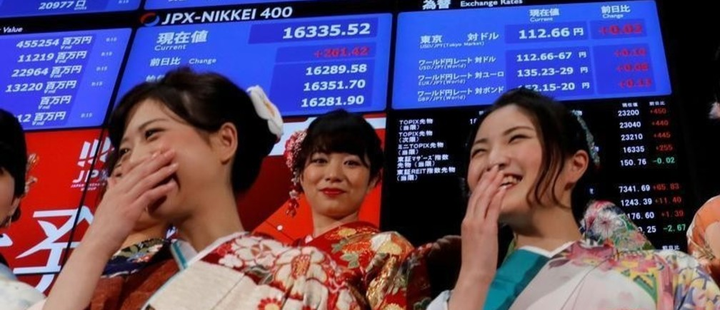 Women, dressed in ceremonial kimonos, smile in front of an electronic board displaying the Nikkei average (top in R) as they pose after the ceremony which kicks off the first day of trading in 2018 at the Tokyo Stock Exchange in Tokyo, Japan January 4, 2018. REUTERS/Kim Kyung-Hoon     TPX IMAGES OF THE DAY - RC1DEA81E690