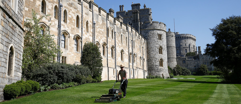 A groundsman mows the lawn outside Windsor Castle in the sun, in Windsor, Britain. April 20, 2018. REUTERS/Henry Nicholls - RC173B9F3BF0