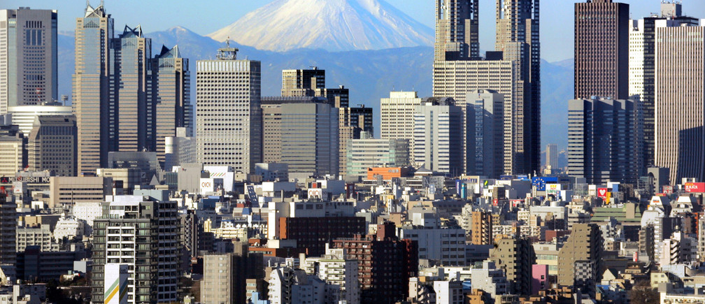 Japan's Mt Fuji, covered with snow, is seen through Shinjuku skyscrapers in Tokyo January 8, 2006. The recovery of Japan's economy has been helped by a strong recovery in exports and a rise in corporate profits that has filtered through to lower unemployment rates and raise incomes. The recovery has bolstered confidence in the stock market, where the Nikkei share average surged 40 percent in 2005. REUTERS/Kimimasa Mayama - RP3DSFDBQPAC