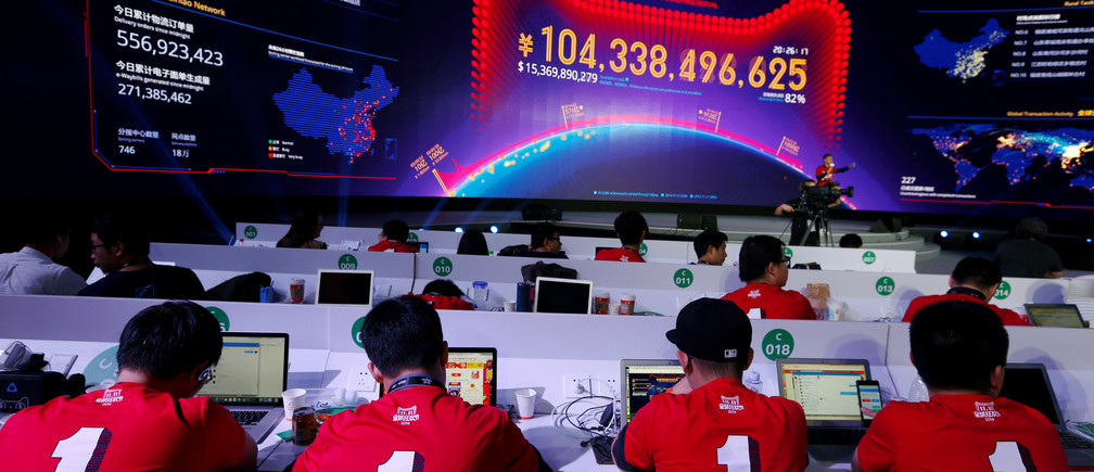 Attendants watch a screen showing the value of goods being transacted at Alibaba Group's 11.11 Singles' Day global shopping festival at a media centre in Shenzhen, China November 11, 2016