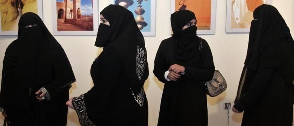 A group of Saudi women look at photographs by a group of Saudi women photographers during the opening of their gallery in Amman April 8, 2009.   REUTERS/Muhammad Hamed (JORDAN SOCIETY)