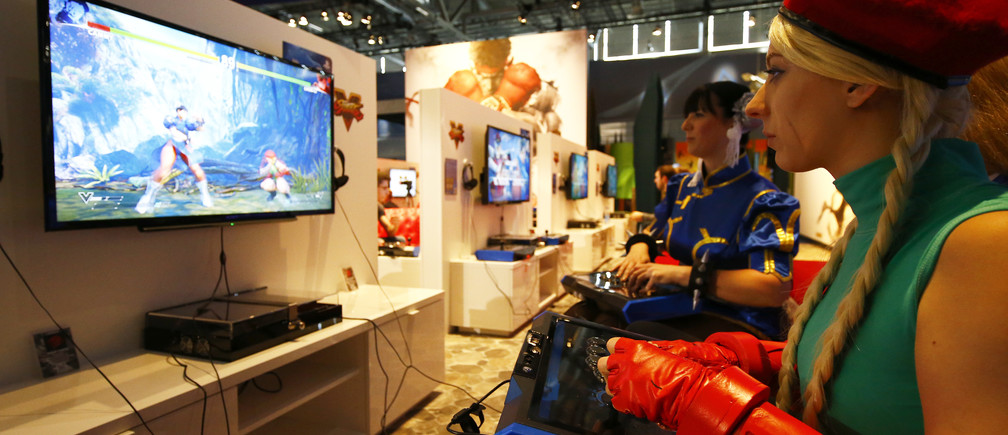 Two women, dressed as videogame Streetfighter's characters Chun-Li and Cammy (R), play the game on a Sony playstation in Cologne, Germany August 5, 2015. The Gamescom convention, Europe's largest video games trade fair, runs from August 5 to August 9. REUTERS/Kai Pfaffenbach  - LR2EB850PI26O