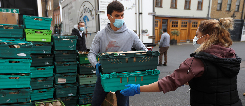 Executive chef of Annabel's private members club Julien Jouhannaud helps to load meals for NHS workers into vans, after they were prepared at their premises in London, Britain, May 11, 2020.  Picture taken May 11, 2020.  REUTERS/Peter Nicholls - RC2MNG92GUM1