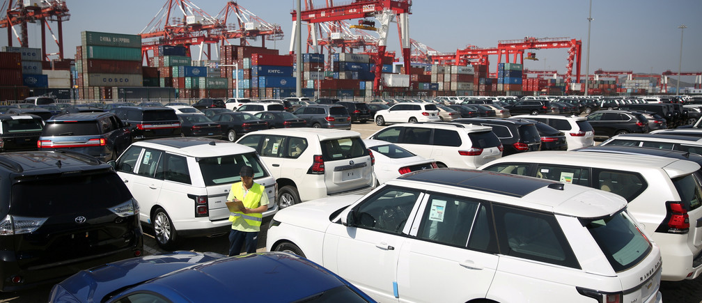 A worker inspects imported cars at a port in Qingdao, China