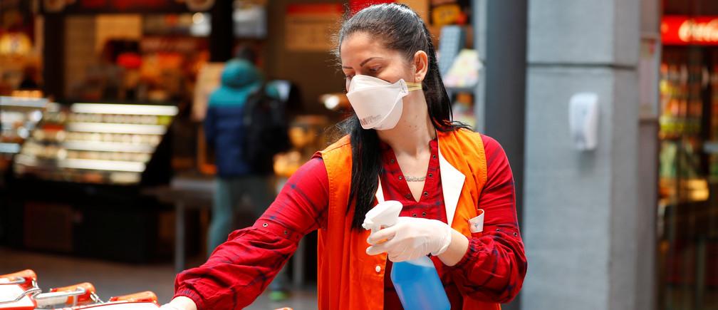 Un empleado de los supermercados Spar con una máscara facial protectora desinfecta los carritos de la compra durante el brote de la enfermedad coronavirus (COVID-19) en Viena, Austria, el 1 de abril de 2020.
