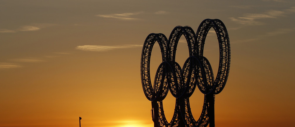 A flight of geese passes the Olympic rings, afloat on a barge in Vancouver's harbour, at dawn as the Vancouver 2010 Winter Olympics continues February 20, 2010. REUTERS/Chris Helgren      (CANADA - Tags: ANIMALS SPORT OLYMPICS IMAGES OF THE DAY) - GM1E62L093701
