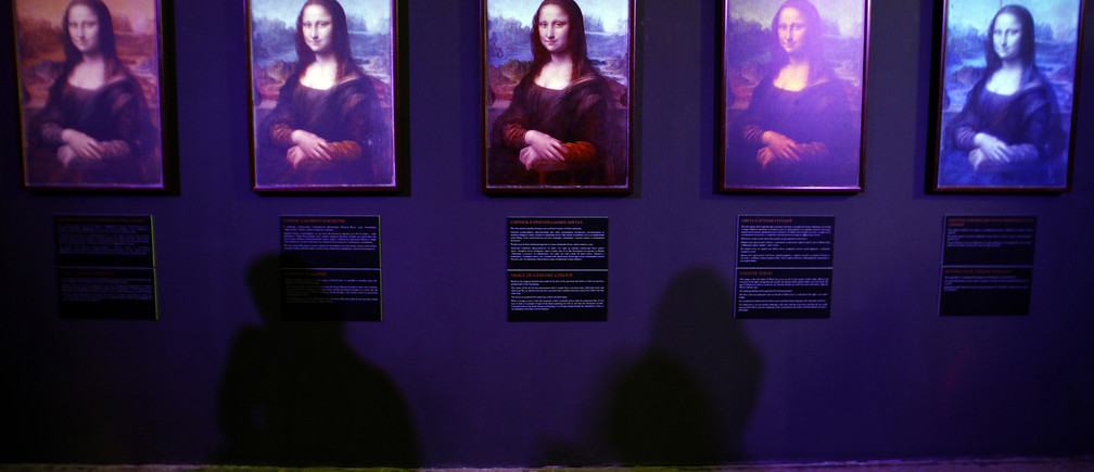 """Visitors cast shadows on photographs, by French engineer Pascal Cotte, of the back of the Mona Lisa  in the exhibition """"Da Vinci - the genius"""" in the Museum of Artillery in St. Petersburg October 5, 2011. Cotte was allowed exclusive access to photograph the Mona Lisa with a specially developed digital camera that captured the look of the famous painting during various stages of its life.  REUTERS/Alexander Demianchuk (RUSSIA - Tags: SOCIETY) - GM1E7A600C001"""