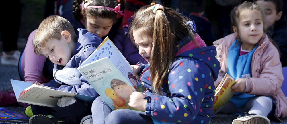 "Children read books at Montevideo's Independencia square while participating in the activity ""Al Aire Libro"" that encourages reading in public spaces, September 4, 2015.  REUTERS/Andres Stapff  - RTX1R5PA"