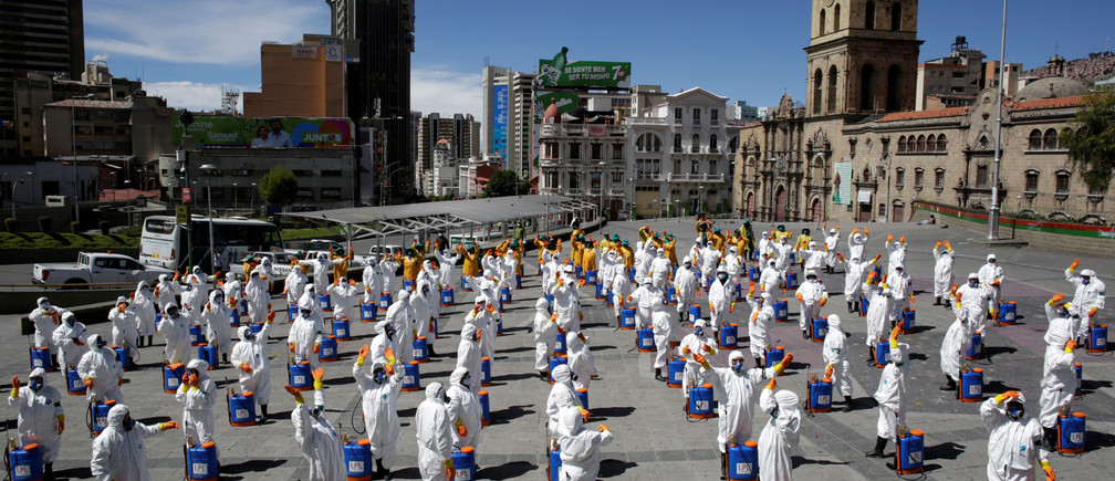 Men and women wearing protective gears and face masks prepare to sanitize at the centre of La Paz, as the spread of the coronavirus disease (COVID-19) continues, in La Paz, Bolivia, April 2, 2020. REUTERS/Manuel Claure - RC2LWF9BEE04