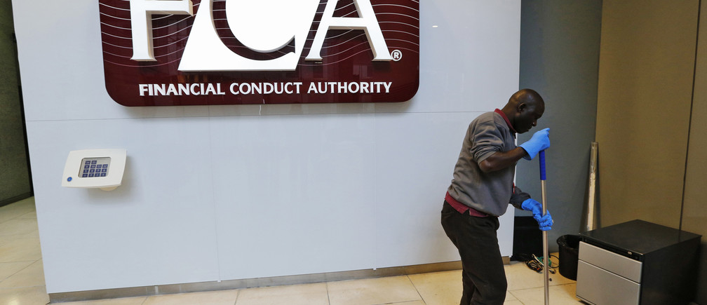 A maintenance worker cleans the entrance area of the headquarters of the new Financial Conduct Authority (FCA) in the Canary Wharf business district of London April 1, 2013. The Financial Services Authority (FSA) has been scrapped from April 1 amid reforms to fix a supervisory system criticised for failing to spot the financial crisis coming, forcing Britain to bail out banks. Two new bodies will replace it - the FCA and the Prudential Regulation Authority.  REUTERS/Chris Helgren (BRITAIN - Tags: BUSINESS POLITICS) - RTXY4O9