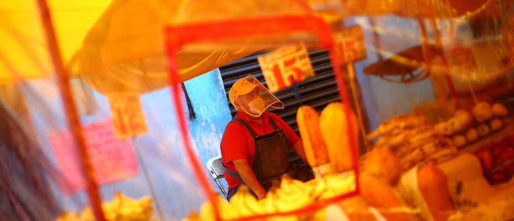 """Un vendedor, que lleva una máscara facial, aparece detrás de una lámina de plástico instalada para protección en un mercado local conocido como """"Tianguis"""", ya que vuelve a abrir bajo estrictas medidas sanitarias después de un cierre de dos meses y el brote de la enfermedad coronavirus (COVID-19) continúa, en el barrio de Iztapalapa en la Ciudad de México, México 15 de junio de 2020."""