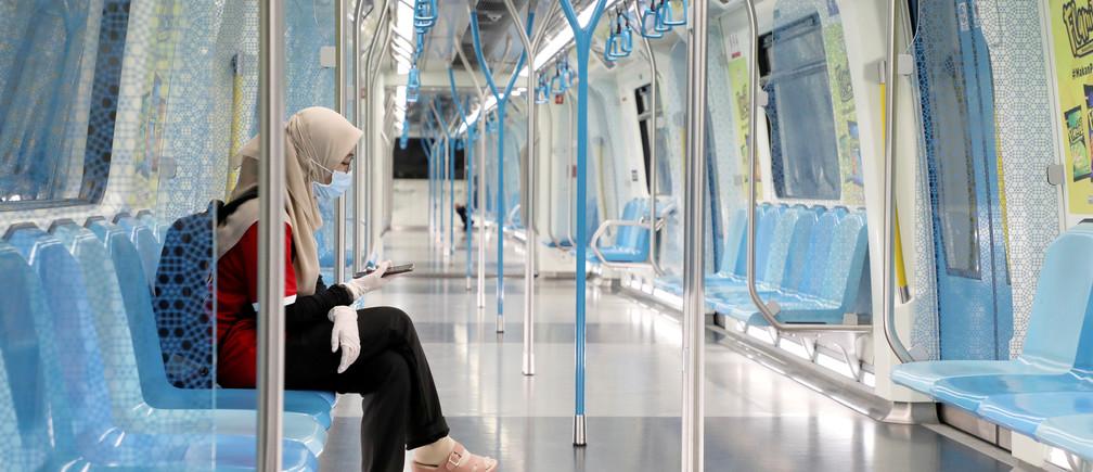 Une femme portant un masque et des gants de protection, utilise son téléphone dans un train de transport en commun rapide, lors de l'ordre de contrôle des mouvements dû à l'épidémie de coronavirus (COVID-19), à Kuala Lumpur, en Malaisie, le 22 mars 2020.