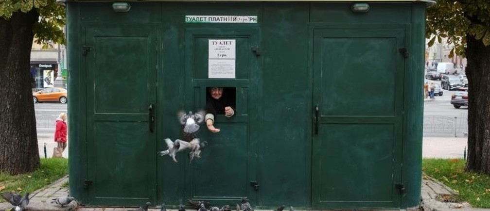 A cashier feeds pigeons and waits clients as she sells tickets to a public toilet in central Kiev, Ukraine September 27, 2019.  REUTERS/Gleb Garanich - RC1580E82040