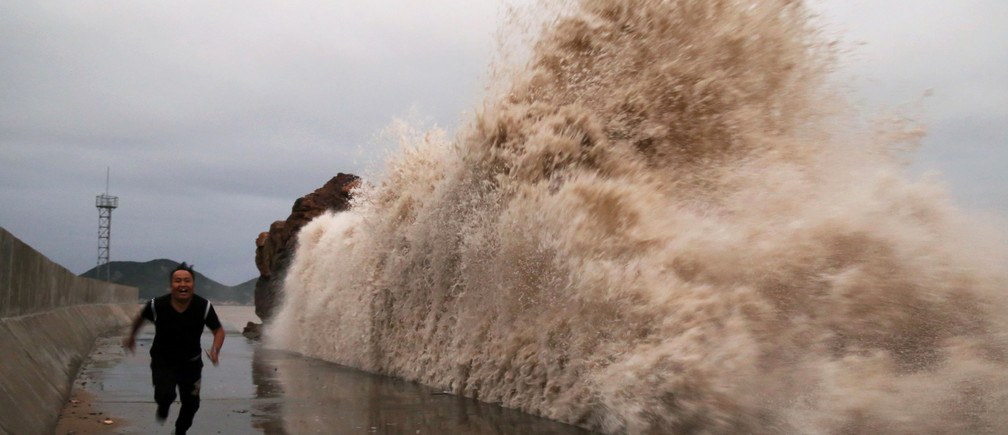 A man runs next to huge waves breaking on the waterfront, as the Typhoon Kong-rey approaches in Taizhou, Zhejiang province, China October 4, 2018.Picture taken October 4, 2018. REUTERS/Stringer ATTENTION EDITORS - THIS IMAGE WAS PROVIDED BY A THIRD PARTY. CHINA OUT.    REUTERS/Stringer CHINA OUT - RC1742299880