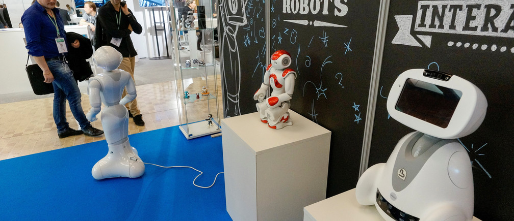 Visitors look at SoftBank humanoid robots named Pepper (L) and Nao (C), and Blue Frog Robotics robot named Buddy (R) at the SIdO, the Connected Business trade show, in Lyon, France, April 6, 2017. REUTERS/Robert Pratta - RTX34EVX