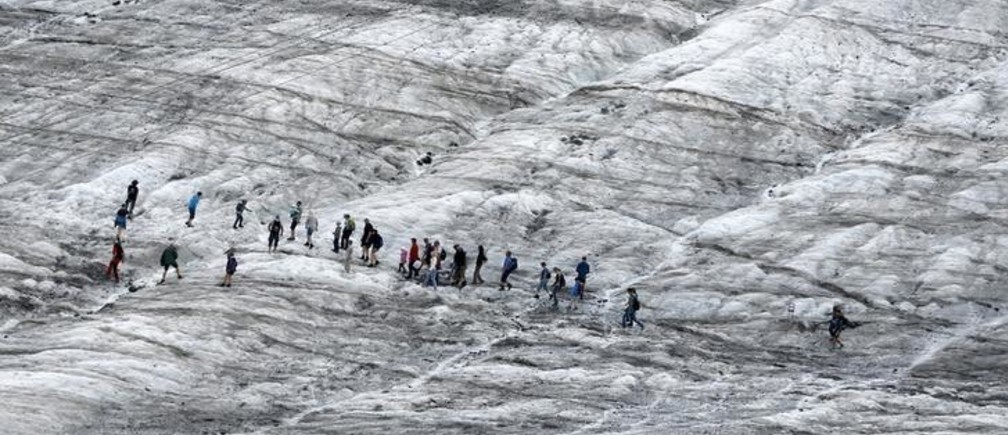 Tourists walk along a glacier during a simulated Mars mission on Tyrolean glaciers in Kaunertal, Austria, August 7, 2015. The Austrian Space Forum is sending some of its researchers to practice weight-less walking in spacesuits on a glacier which resembles the terrain on Mars. REUTERS/Dominic Ebenbichler
