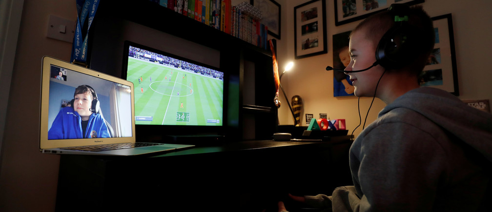 Evan Smith (12) plays online video games with his friend Alex White (12) while communicating through FaceTime at Ouston, as the spread of coronavirus disease (COVID-19) continues, Ouston, Britain, March 24, 2020. REUTERS/Lee Smith - RC2FQF99QTZV