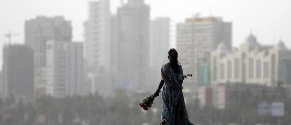 A flower seller looks for possible buyers at a seafront in Mumbai June 25, 2008. REUTERS/Arko Datta (INDIA)