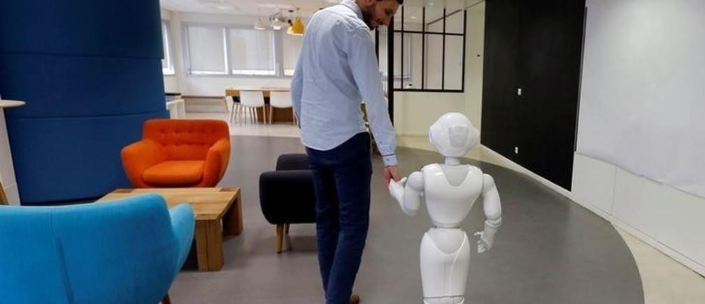An employee of SoftBank Robotics walks with the Robot Assistant Pepper in Paris, France, March 9, 2018. Picture taken March 9, 2018. REUTERS/Regis Duvignau