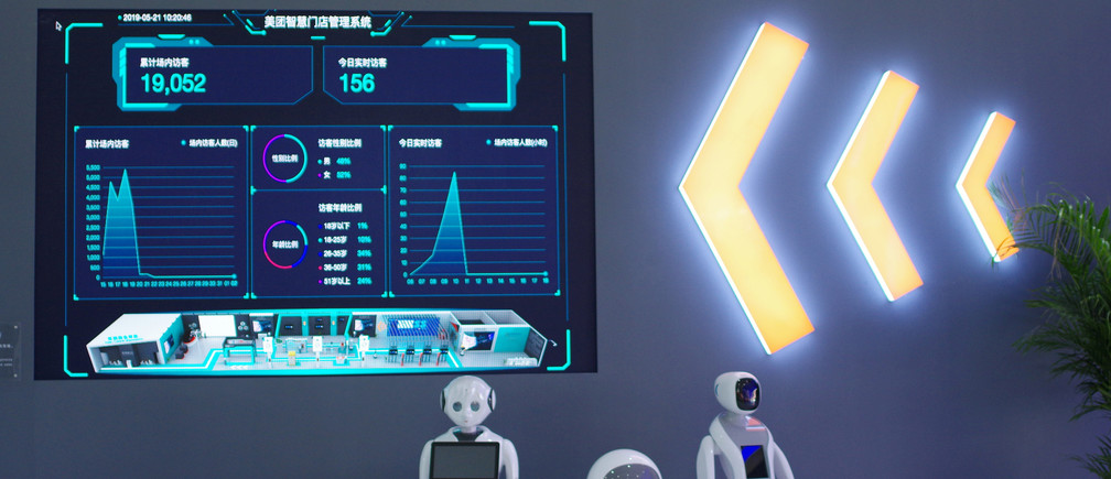 Robots are seen next to a screen showing Meituan's smart retailing management system at the Asian Cuisine Festival, held as a sideline event of the Conference on Dialogue of Asian Civilizations (CDAC), in Beijing, China May 21, 2019. Picture taken May 21, 2019. Qin Cansong/Qianlong.com via REUTERS  ATTENTION EDITORS - THIS IMAGE WAS PROVIDED BY A THIRD PARTY. CHINA OUT.  NO COMMERCIAL OR EDITORIAL SALES IN CHINA.