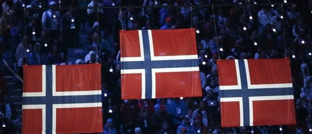 Three Norway's flags are seen during the women's cross-country 30km freestyle victory ceremony, during the closing ceremony for the 2014 Sochi Winter Olympics, February 23, 2014.  REUTERS/Grigory Dukor (RUSSIA  - Tags: OLYMPICS SPORT)
